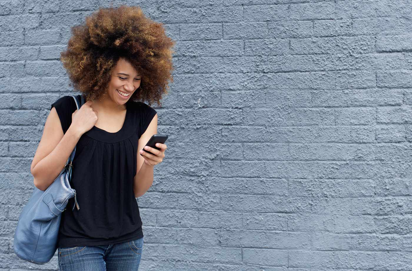 smiling-woman-walking-and-looking-at-mobile-phone